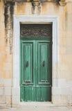 Green Wooden Doors with Black Metal Knockers Stock Photo