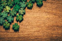 Green wooden four leaf shamrocks on wooden board. Green wooden four leaf shamrocks laying on a wooden board. St. Patrick`s day. Irish culture royalty free stock photo