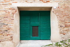 Green wooden gate in old brick wal Royalty Free Stock Image