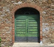 Green wooden gate in old stone Italian house. Green wooden gate in an old stone Italian house, Tuscany, Italy stock image
