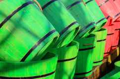 Green wooden half barrels. Green and red wooden garden half barrels for patio planting. Piled in a row Stock Images