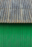 Green wooden house wall, vertical stripes. Rusty metal slate roo Stock Images