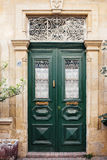 Green wooden mediterranean door. The classical architecture of the Mediterranean (Greece, Italy, Spain, Cyprus, Portugal). Wooden green door on the yellow stone stock photo