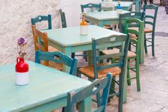 Green wooden outdoor tables and chairs of an italian restaurant stock image