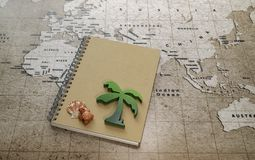 Green wooden palm tree and red turtle with sea shell on notebook on world map. Green wooden palm tree and red turtle with sea shell on notebook on brown world royalty free stock photos