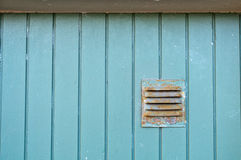 Green wooden panel. Old green wooden panel with a ventilator Stock Image