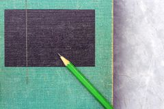 A green wooden pencil is placed on the hardback or textbook. selective focused stock photos