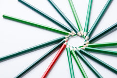 Green wooden pencils arrange as circular with one of different red pencil try to close the gap , light background Royalty Free Stock Photo