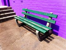 Bench seat against brick wall. Green wooden seating with bright purple wall stock images