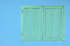 Green wooden window on blue cement wall. Closed green wooden window on blue cement wall background Royalty Free Stock Images