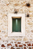 Green wooden window on a stone wall Stock Photo
