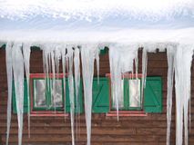 Green wooden windows with  ice stalactites Royalty Free Stock Photography