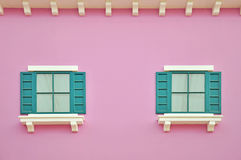 Green wooden windows on pink wall.  Royalty Free Stock Photo
