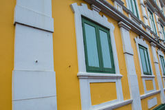 Green wooden windows on the yellow wall Royalty Free Stock Photography