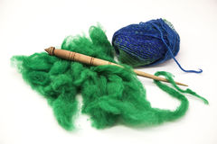 Green wool, blue thread and old spindle close-up on white background. Tools for knitting of wool Royalty Free Stock Photography