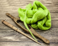 Green wool and old spindle close-up on wooden background. Tools for knitting of wool Royalty Free Stock Image