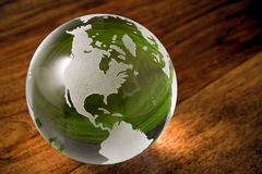 Green world with copyspace. Green globe on wooden desk with copyspace royalty free stock photos