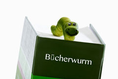 Green worm figure on book Royalty Free Stock Images
