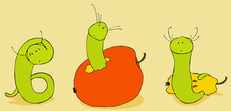 Green Worms. Three green amusing worms eat red apples Stock Images