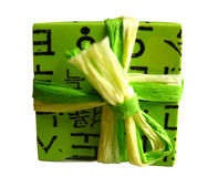 Green wrapped gift box. A gift wrapped in decorative green paper with a yellow and green ribbon isolated against a white background Royalty Free Stock Images