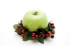 Green wreath with apple. Green wreath with red berries and apple Royalty Free Stock Image