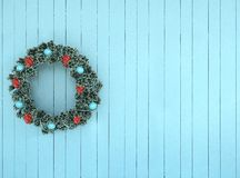 Green wreath with blue and red bow on antique teal aqua rustic wood Stock Image