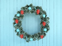 Green wreath with blue and red bow on antique teal aqua rustic wood Stock Photo