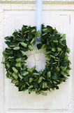 Green wreath on door. Green wreath hanging on cracking wooden door Stock Photography