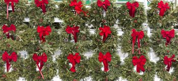 Green wreaths with red bows for sale. Green wreaths with red bows and pin cones hanging from a fence to be dold for Christmas decoration Royalty Free Stock Photos