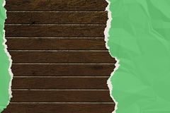 Green wrinkled paper ripped on the wooden board. Stock Image