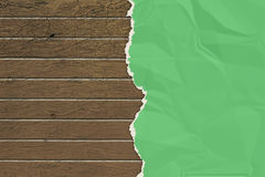 Green wrinkled paper ripped on the wooden board. Royalty Free Stock Images