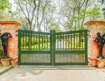 Green Wrought Iron Gate with Statue Stock Image