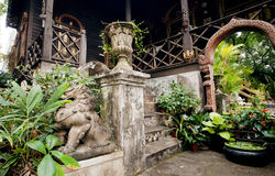 Green yard ancient estate in Thailand, with stone steps and traditional statues at the entrance Stock Photos
