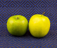 Green yellow apple stands on a blue tablecloth relief Royalty Free Stock Image