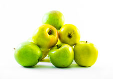 Green and yellow apples forming a pyramid on a white background Royalty Free Stock Photos