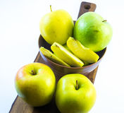 Green and yellow apples and slices in a violet cup on a wooden board on a white background Stock Photography