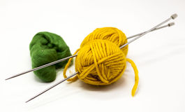 Green and yellow balls of yarn for knitting with spokes on a white background. Royalty Free Stock Images