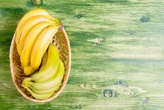 Green and yellow banana in a wicker basket on a green chalkboard Royalty Free Stock Photos