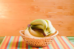 Green and yellow bananas in a wicker basket on green blackboard Royalty Free Stock Image
