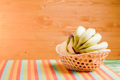 Green and yellow bananas in a wicker basket on green blackboard Royalty Free Stock Photography