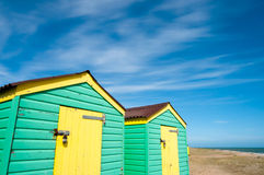 Green and yellow  beach huts in summer Stock Images