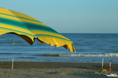 Green and yellow beach umbrella on the sunny beach in summer Royalty Free Stock Image
