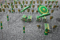 Green and yellow beach umbrellas and deckchairs on stony beach Stock Photo