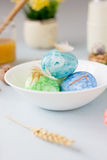 Green, yellow and blue easter eggs on ceramic bowl, bright and airy shot. Royalty Free Stock Photo