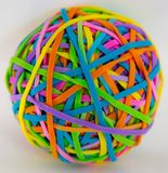 Concept creativity isolated ball colorful rubber bands. Green yellow blue orange rubber elastics office conceptual Royalty Free Stock Photo