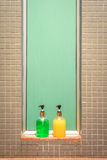 Green and yellow bottles of soap and shampoo against green glass and tiled wall Stock Photo