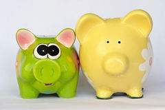 Green and yellow ceramic piggy banks. With flowers posing Royalty Free Stock Photography