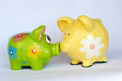 Green and yellow ceramic piggy banks. With flowers sniffing Stock Photo