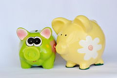 Green and yellow ceramic piggy banks. With flowers speaking Stock Photography