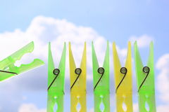 Green and yellow clothes pins sky Royalty Free Stock Image